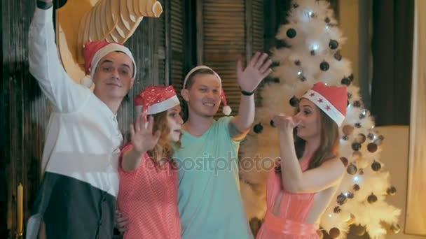 Šťastné, veselé skupina přátel na vánočním večírku. Pozdrav do kamery, Bavíte se usmívající se slaví Silvestr
