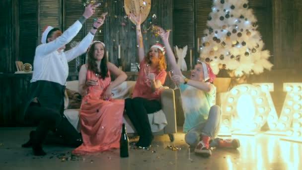 Skupina přátel slaví Štědrý den doma. Házení konfet, smích, zábavu