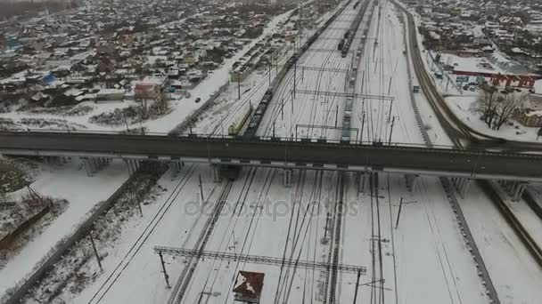 Aerial. Freight train with cargo containers passing railway station.