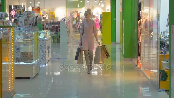 Fiatal nő séta a bevásárló szatyrok mall.