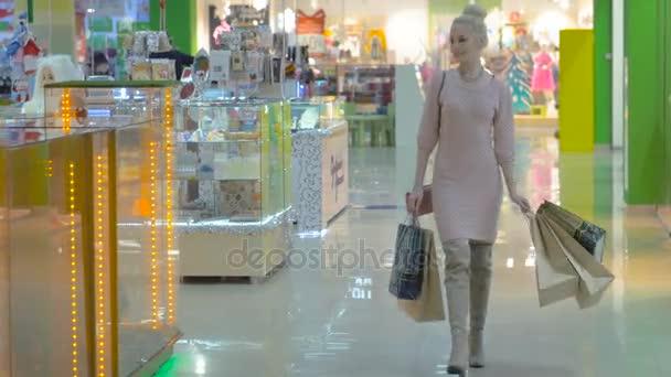 Mladá atraktivní dívka procházky v nákupním centru s nákupní tašky