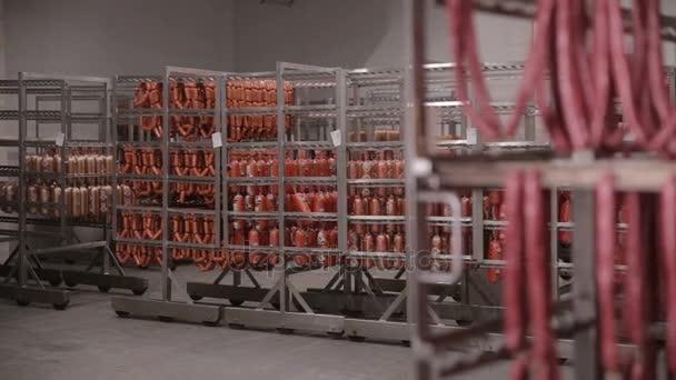 Skladování potravin, sklad. Masné výrobky, klobásy zavěšené na regály ve skladu masa, mrazák