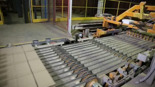 Průmyslový robot dopravník pracuje v továrně, kompletace zboží, cihly
