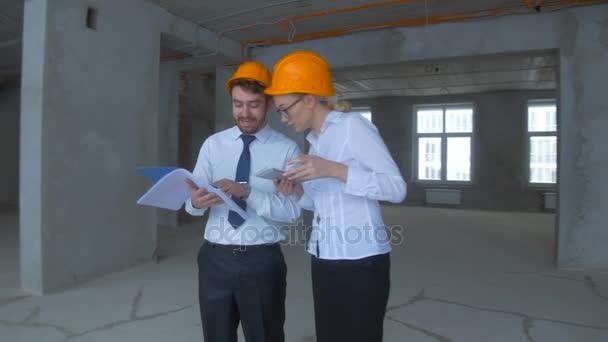 Tým odborníků - konstruktér a architekt - kontrola nedokončené průmyslové stavby, staveniště.