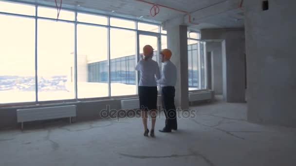 Podnikatel a podnikání žena v obleku, čepice v nové nedokončené kancelářská budova komunikovat, diskutovat plán staveniště