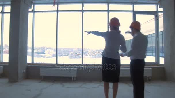 Businessman and business woman in suit, hard hat in a new unfinished office building communicate, discuss blueprint, construction site.