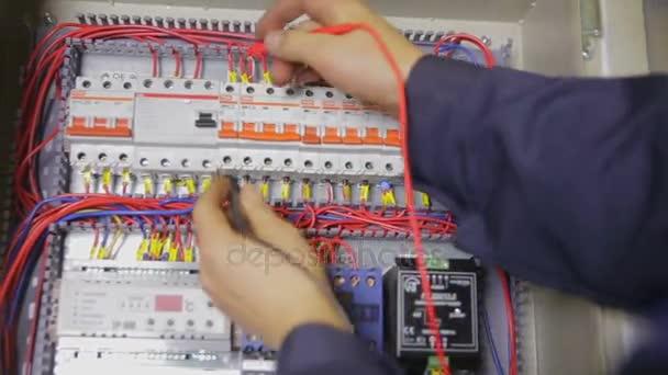 Elektrikář, práce s jistič, tester, multimetr v pojistkové skříni.