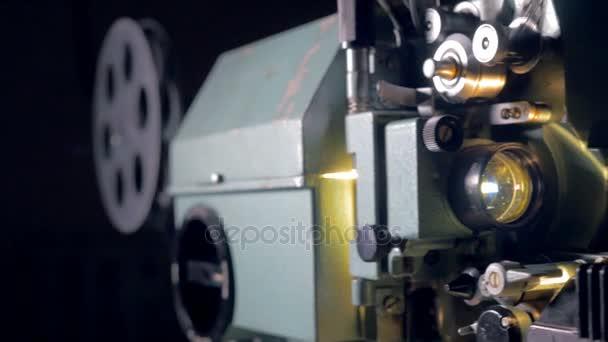 Filmový projektor. Stará promítačka pracovat potmě. Zvuk. Dolly zastřelen. Detailní záběr