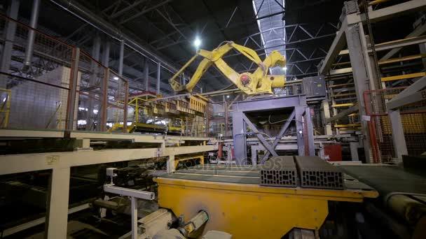 Průmyslová automatizace. Robotické rameno montáž nové stavební materiály na dopravní pás.