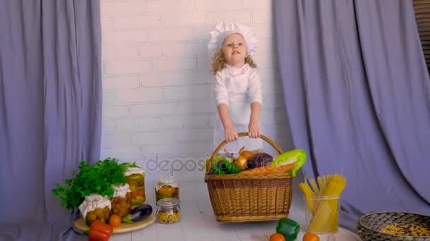 lächelnd liebenswertes Kinderhebekorb mit gesundem Essen, Gemüse. Konzept der gesunden Ernährung.