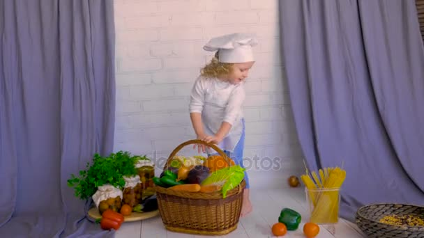 Girl in chef hat carring basket with fresh Vegetables. Healthy food concept.