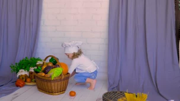 Nettes Kind legte Gemüse in Korb. Konzept der gesunden Ernährung
