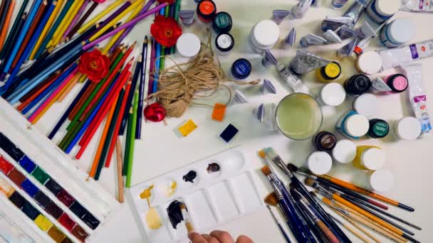 Artist mixing colors in palette. Stylish top view of artists desk.
