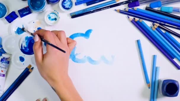 Blue palette. Rain, blue cloud with drops painted on a paper. Artist desk from above. Top view.