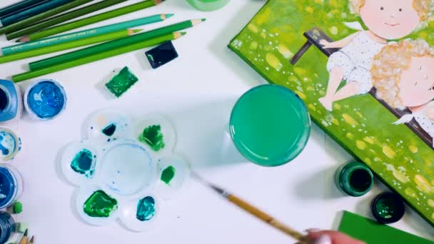 Artist desk with abstract green items. Artist choosing green shade. Top view.