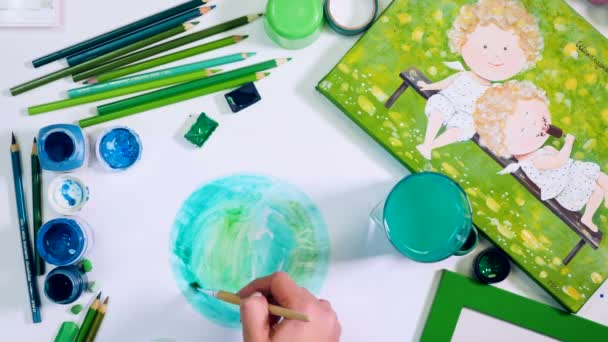 Hands drawing earth. Artist desk from the top. Green palette.