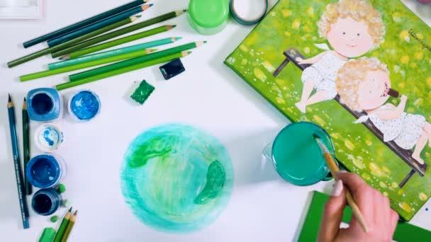 Zelená paleta. Ruce, kreslení země. Umělec stůl shora. Timelapse.