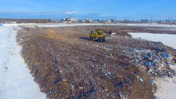 Aerial: tractor working at the garbage dump. Landfill, garbage dump, trash dump from above.