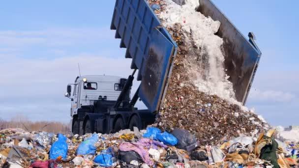 4K. Truck offloading waste into a huge landfill.
