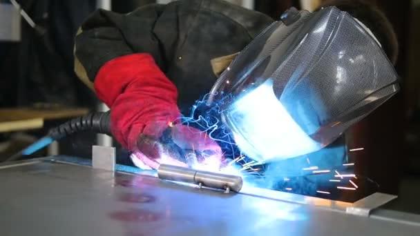 Svářečka v ochranné oděvy pracující s kovem, svařování kovů. Zpomalený pohyb.