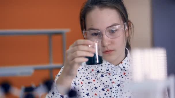 Chemik školy dívka 10-11 let v brýlích míchání chemikálií ve zkumavce