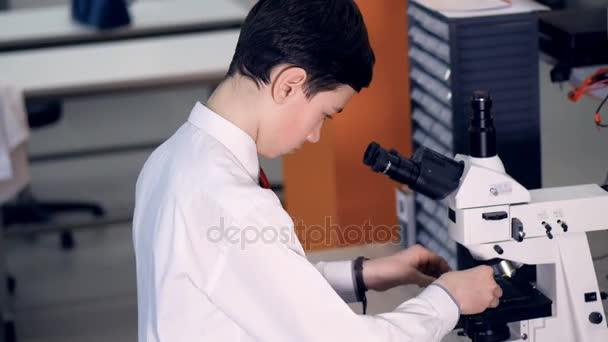 Teen im schullabor studiert biologie mikroskop durchsehen