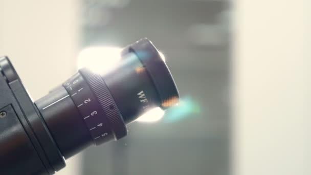 Teen schulmädchen im labor studiert biologie mikroskop durchsehen