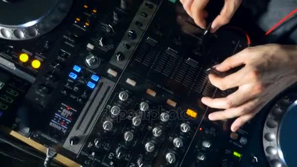 Detail z rukou dj pomocí směšovače a gramofony v nočním klubu.