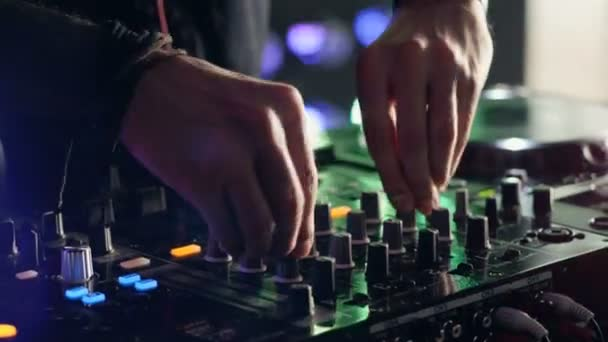 Close-up. Hands of DJ tweak various track controls on DJ mixer console at nightclub party.