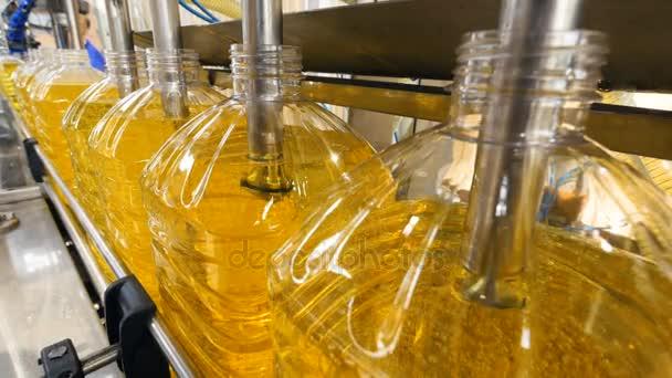 Detail. Průmyslové dopravník s plastové láhve naplněné žlutá tekutina. 4k