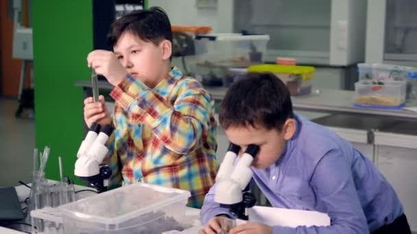 Az iskola fiú a tudomány laboratórium dolgozik. Közelről. 4k.