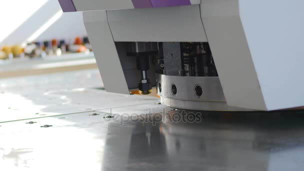 The machine making perforation on the steel sheet. Close-up. 4K.