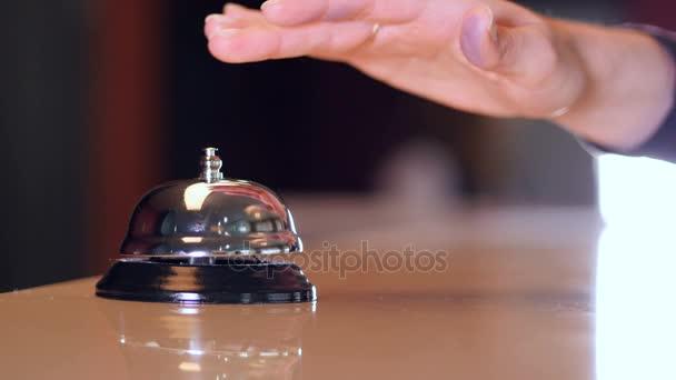 Man ruft an einer alten Hotelglocke auf einem Holzständer an und holt den Chipschlüssel aus dem Hotelzimmer. 4k.