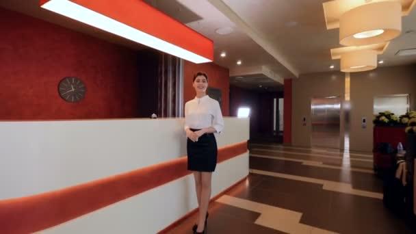 Usměvavý recepční v hotelové recepci seznámit hosty. 4k