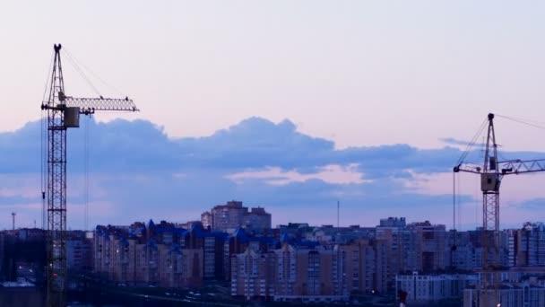 Jeřáb pracuje při západu slunce. Staveniště s budovami města na pozadí. Timelapse. 4k