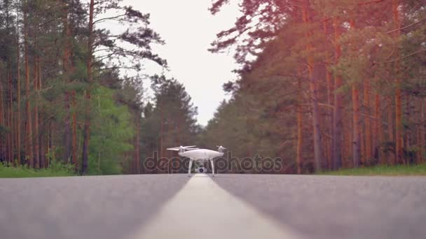 Quadrocopter drone take off on a road. Super slow motion.