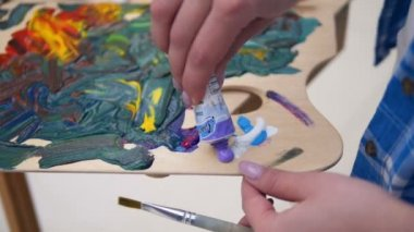 Female artist mixing colors, close up.
