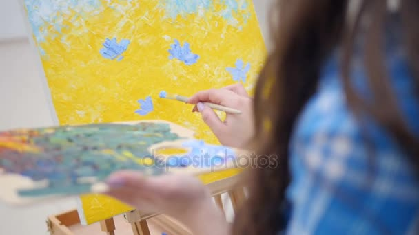 Woman painting blue flowers on yellow background.