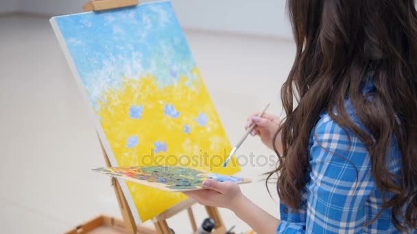 Girl painting blue flowers on a canvas.