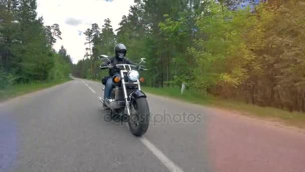 Motocyklista na motocyklu rychle na prázdné silnici.