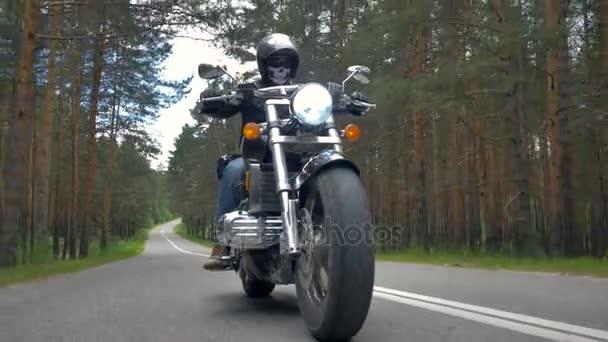 Biker pomalu na motocyklu na prázdné silnici.