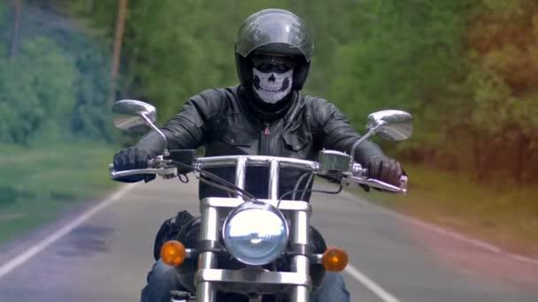 Motocyklista, biker na osamělé silnici, jednotky s maskou lebky. 4k.