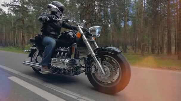 Motorkář v černých jízd po prázdné silnici dva jízdní pruhy. 4k