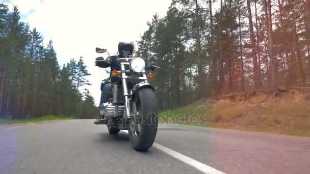 Nízkou pohled na motocyklista na koni zpevněné lesní cestě.