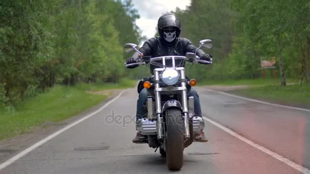 Zkušený biker jízda motocyklů na asfaltové silnici.