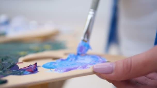 Artist blending paint on the palette. 4K.