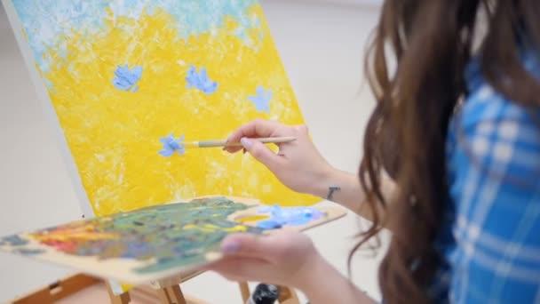 Frau Maler malen mit Ölfarben auf einem weißen Papier. 4k.