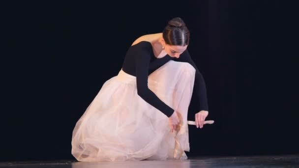A ballerina ties up her white shoe.