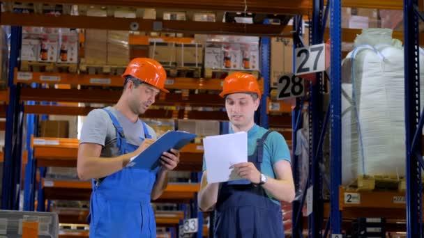 Lagerarbeiter in harter Arbeit in einer Lagerhalle zwischen Lagerregalen. 4k.
