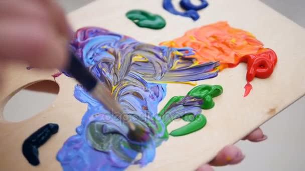 Malíř ruce prolnutí živé barvy na paletě. 4k.